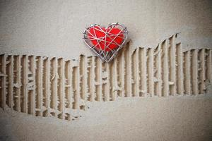 red heart on torn grunge cardboard paper