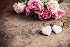 hartvorm met roze roze bloem op houten tafel
