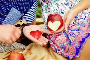 vrouwenhand met appel, die een hart sneed