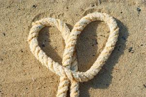 touw met een hartknoop - zand achtergrond