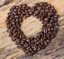 Heart shape made from coffee beans on wooden