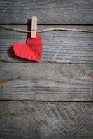 Red heart hanging on the clothesline. On old wood background.