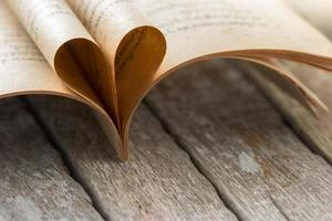 Heart shape from opened book pages on wooden background.