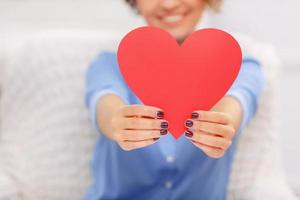 Cheerful girl holding heart