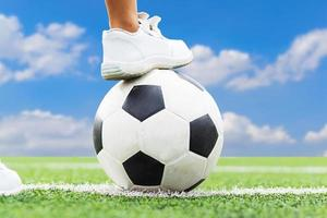 Feet of a boy wearing white sneakers stepping on a soccer ball.