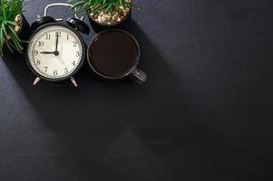 taza de café y un reloj en el escritorio foto