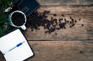 cadernos, caneta e grãos de café na mesa foto