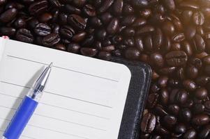 caderno e caneta em grãos de café foto