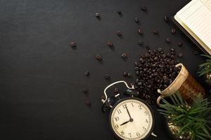 grãos de café, relógio e um notebook foto