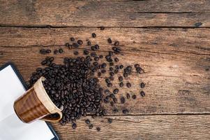 grãos de café e caderno na mesa foto