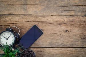 smartphone, relógio e grãos de café na mesa foto