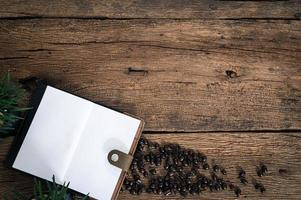 caderno e grãos de café na mesa foto