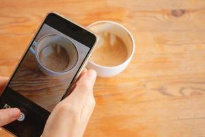 A woman uses cellphone to take a photo of a cup of hot coffee