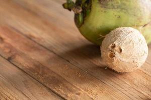 Cáscara de coco seca sobre fondo de mesa de madera