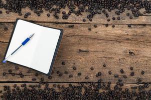caderno, caneta e grãos de café na mesa foto