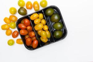 Cherry tomatoes in and around a black box