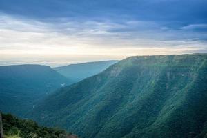 sommet de la montagne verte au coucher du soleil photo