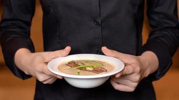 camarero sosteniendo sopa de champiñones