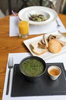 Green soup on a black plate
