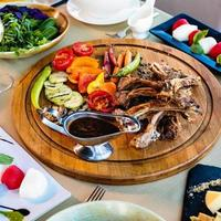 Kebab and vegetables on round wooden spinning plate