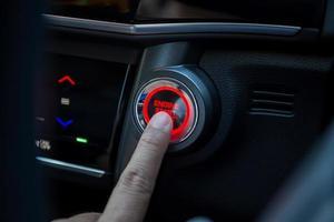dedos pressionando o botão de partida do carro foto