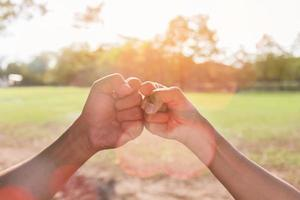 Two people fist bumping photo