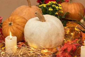 abóbora branca de halloween com velas e palha