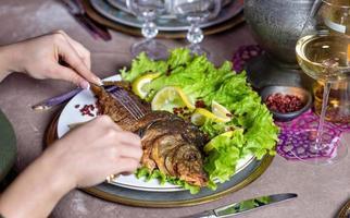 mujer comiendo un pescado entero