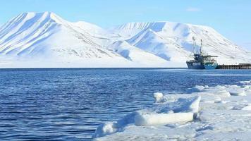 navio de carga em um porto norueguês no fundo de montanhas nevadas. video