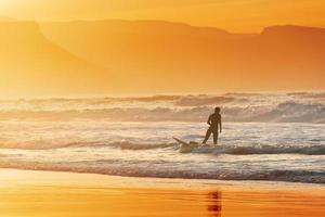 surfer exiting water at sunset photo