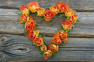 Roses in heart shape on wooden background