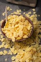 Flocons de maïs dans un bol en bois avec cuillères et coeur rouge