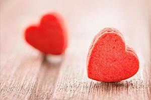 Two red heart shaped cookies, extreme close up, selective focus,