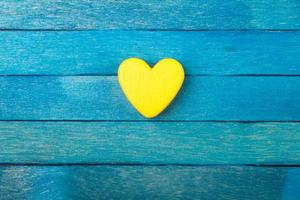 Decorative yellow heart on blue wooden background