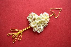 Corazón de San Valentín hecho de alambre sobre fondo rojo. foto