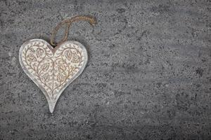 coração de madeira esculpido em fundo de pedra cinza