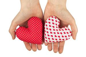 Woman hands holds two home made stuffed textile hearts