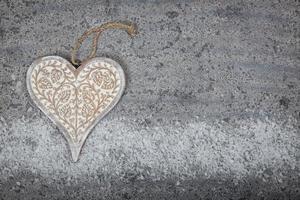 corazón de madera sobre fondo de piedra gris foto