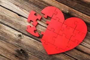 Corazón de rompecabezas rojo sobre fondo de madera marrón