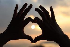 las manos hacen una forma de corazón en la playa al atardecer foto