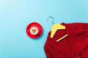 xícara de cappuccino e suéter vermelho