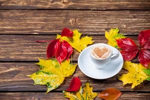 folhas de outono e xícara de café na mesa de madeira.