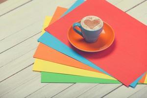 xícara de café e papel de cor na mesa de madeira.
