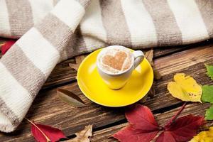 folhas de outono, lenço e xícara de café na mesa de madeira.