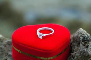 Wedding ring with heart shape symbol on beach rock