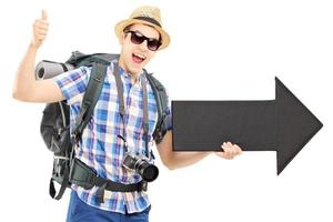 Tourist with backpack holding big black arrow and giving thumb