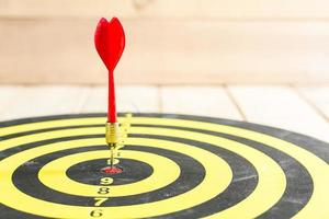 Red dart arrow hitting in the target center of dartboard photo