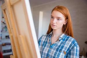 Concentraited attractive female artist painting on canvas in art workshop