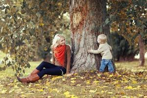Happy mother and child having fun in autumn photo