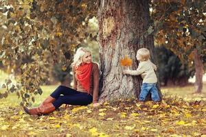 Family in autumn park! Happy mother and child having fun photo